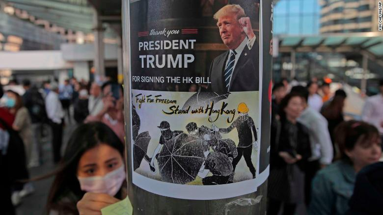 Protesters stick a poster featuring US President Donald Trump on a pillar during a demonstration in Central, the financial district of Hong Kong.