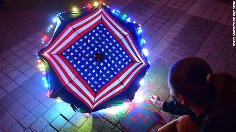 A protester sits beside a thank you note and an umbrella bearing patterns of the US flag.