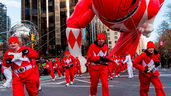 Parade volunteers fight with winds as they hold a Power Rangers balloon on Columbus Circle.