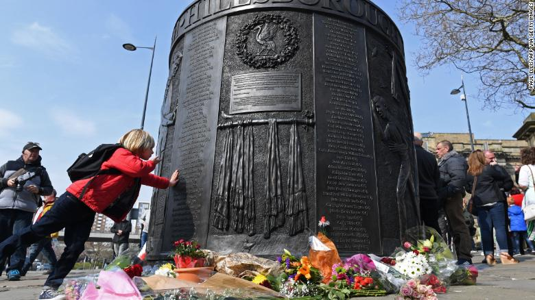 People touch the Hillsborough Memorial Monument, where the names of the victims have been written in perpetuity.