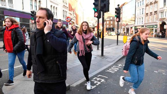 People rush away from Borough Market after police told them to leave the area.