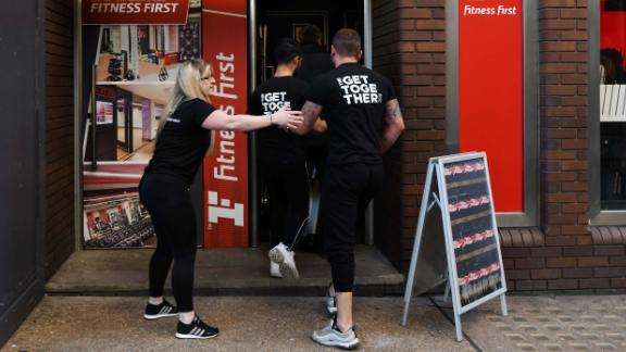 Staff members are ushered into a Fitness First gym after reports of shots being fired.