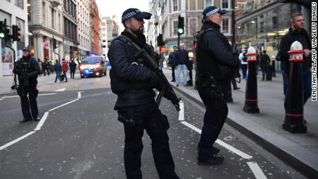 Armed policman stand guard at Cannon Street station in central London, on Friday.