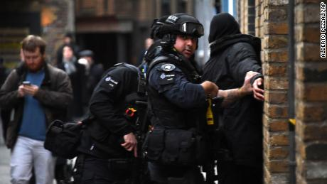 Police apprehend a man in a street on the south side of London Bridge on Friday.