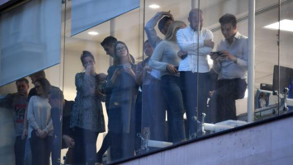 Office workers watch from windows as the police carry out an operation following the terrorist attack.
