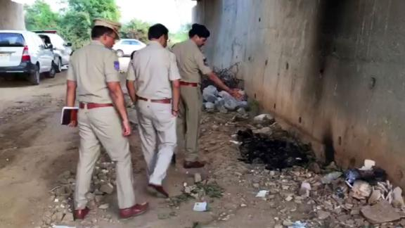 Indian police officers inspect the site where they found the burned body of a 27-year-old woman in an underpass on the outskirts of Hyderabad.