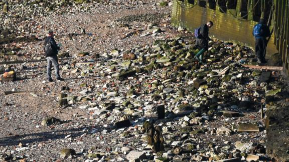 Forensic officers examine the river Thames bank under London Bridge.