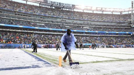Workers cleared the line markers of snow during the game between the New York Giants and the Green Bay Packers at MetLife Stadium.