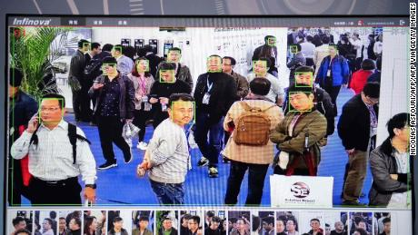 A screen shows visitors being filmed by AI security cameras with facial recognition technology at the 14th China International Exhibition on Public Safety and Security at the China International Exhibition Center in Beijing on October 24, 2018.