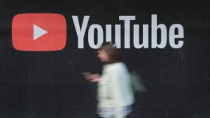 BERLIN, GERMANY - SEPTEMBER 27: A young woman with a smartphone walks past a billboard advertisement for YouTube on September 27, 2019 in Berlin, Germany. YouTube has evolved as the world's largest platform for sharing video clips. (Photo by Sean Gallup/Getty Images)
