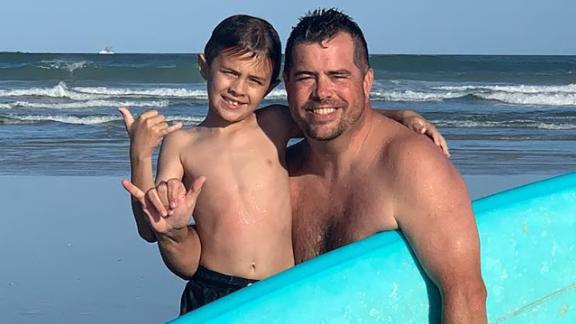Chandler Moore and his dad, Shaun, at the beach on Saturday after the shark encounter.