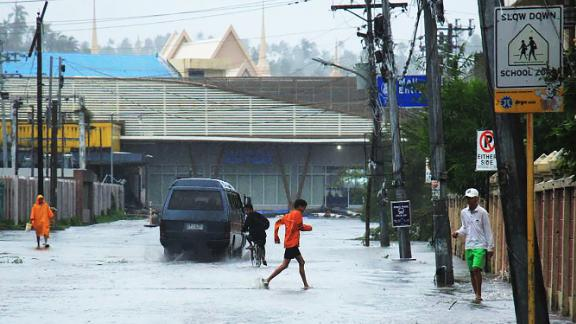 A child (C) wades through a flooded road following the passage of Typhoon Kammuri in Legaspi City, Albay province, south of Manila on December 3, 2019. - Typhoon Kammuri lashed the Philippines with fierce winds and heavy rain, as hundreds of thousands took refuge in shelters and the capital Manila prepared to shut down its international airport over safety concerns. (Photo by RAZVALE SAYAT / AFP) (Photo by RAZVALE SAYAT/AFP via Getty Images)