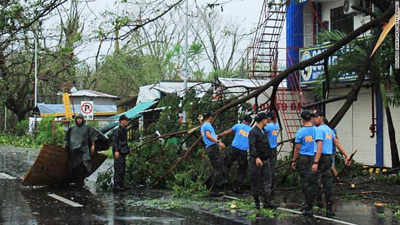 Policemen remove branches from a damaged tree following the passage of Typhoon Kammuri south of Manila.