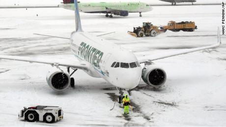Ground crews remove snow from the airport tarmac as flights resume after an overnight snowfall, at the Albany International Airport in Colonie, N.Y., on Monday, Dec. 2, 2019. (AP Photo/Hans Pennink)