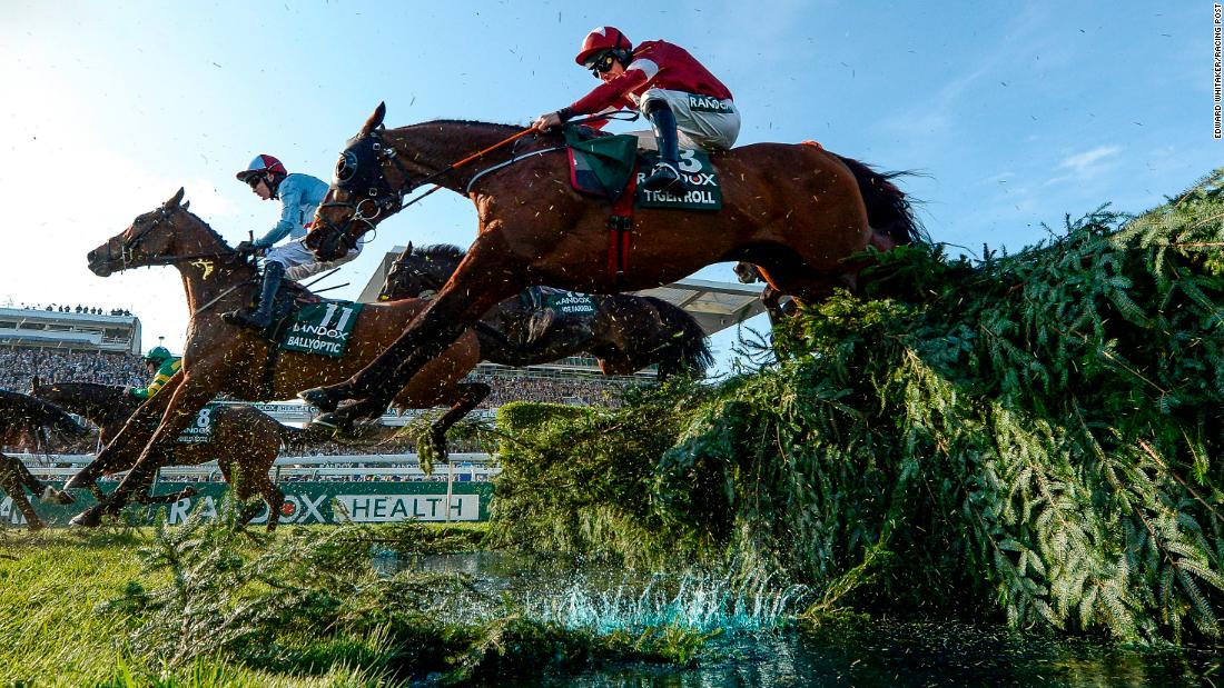 "This picture of two-time Grand National winner Tiger Roll jumping to success for the second time is one of his favorites. The photograph was taken remotely but Whitaker credits the birch hitting to water for ""bringing it to life""."