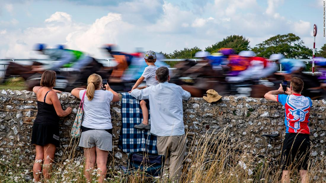 "This picture was inspired by the Tour de France which was taking place at the same time as the horse race. The family of spectators were watching runners at Goodwood flash past but Whitaker said it ""could have easily been cyclists speeding past."""
