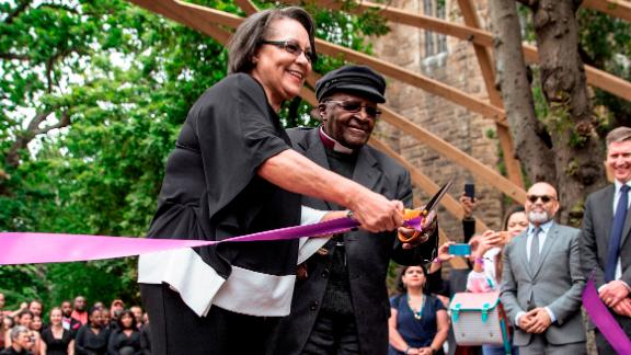 """Tutu, accompanied by Cape Town Mayor Patricia de Lille, cuts a ribbon to unveil the """"Arch for the Arch"""" in 2017. The architectural structure commemorates Tutu's life and work and also represents the 14 chapters of the South African constitution."""