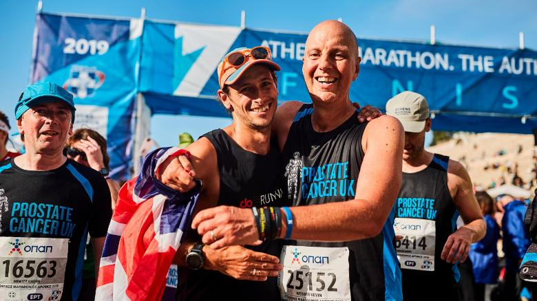 Butter (left) celebrates at the finish line in Athens with close friend Kevin Webber -- the inspiration behind the trip.