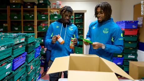Moise Kean and Alex Iwobi help sort stock at North Liverpool food bank.