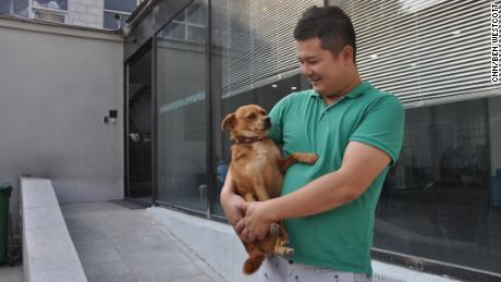 Joypets Funeral Home founder Li Chao holds one of his dogs at his workplace in Beijing in October.