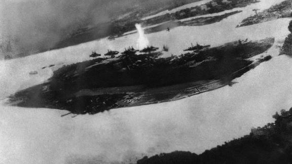 This is believed to be an image of the first bomb on Pearl Harbor; it shows a Japanese plane pulling out of a dive near the explosion.