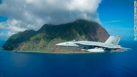 A US Navy F/A-18E Super Hornet jet flies past the island of North Iwo Jima in 2016.