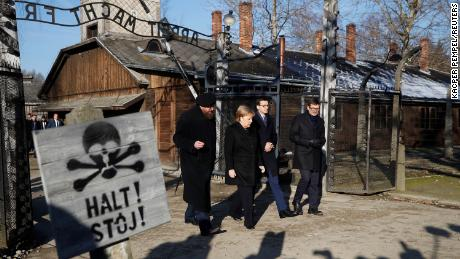 "German Chancellor Angela Merkel, Poland's Prime Minister Mateusz Morawiecki and museum director Piotr Cywinski walk past the ""Arbeit Macht Frei"" gate at the former Nazi German concentration and extermination camp Auschwitz in Oswiecim, Poland, December 6, 2019. REUTERS/Kacper Pempel"
