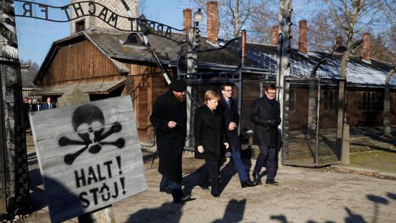 "Merkel, Morawiecki and the Auschwitz museum director Piotr Cywinski walk past the ""Arbeit Macht Frei"" gate in the former Nazi death camp."