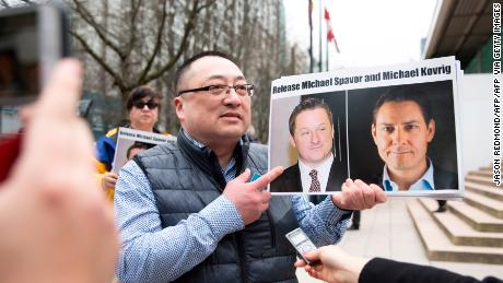 A campaigner holds photos of Canadians Michael Spavor and Michael Kovrig, who are being detained by China, in Vancouver, on March 6, 2019.