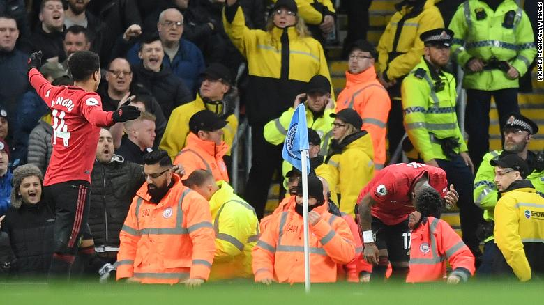 Fred of Manchester United reacts after being struck by an item thrown by Manchester City fans.