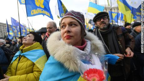 Protesters draped in Ukrainian flags rally against Zelensky's Donbas peace plan.