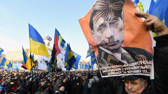 "TOPSHOT - An activist holds a poster depicting Russian President Vladimir Putin as people gather for a mass rally called ""Red lines for ZE"" (Ukrainian President's nickname) to demand ""no capitulation"" to Russia, at the Independence Square in Kiev, on December 8, 2019, ahead of a summit in Paris aimed at ending the hostilities between Ukraine and Russia. - France's President, Germany's Chancellor, Ukraine's President and Russia's President will take part in a December 9 summit in Paris, moderated by the leaders of France and Germany, aimed at ending more than five years of fighting between the two countries. (Photo by Sergei SUPINSKY / AFP) (Photo by SERGEI SUPINSKY/AFP via Getty Images)"