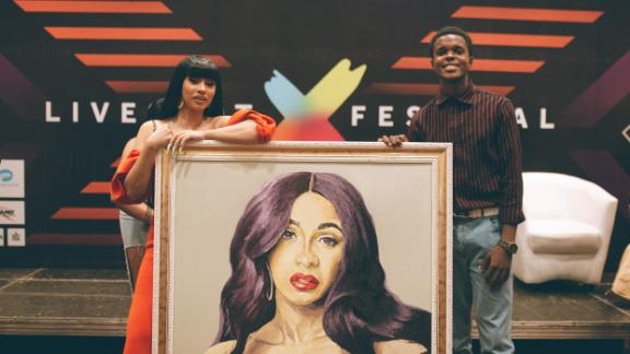 Award-winning rapper, Cardi B, receives painting from Nigerian artist during her visit to the West African country. Photo by Faje Kashope