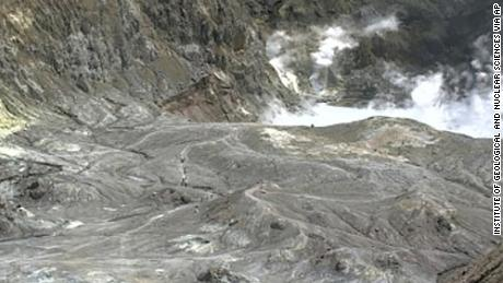 In this image released by GeoNet, tourists can be seen on a trail near the volcano's crater Monday, Dec. 9, 2019, on White Island, New Zealand.
