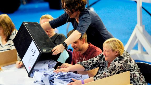 Staff members empty a ballot box at the main Glasgow counting centre in Emirates Arena in Glasgow, Scotland, on June 8, 2017, after the polls closed in Britain's general election. Prime Minister Theresa May is poised to win Britain's snap election but lose her parliamentary majority, a shock exit poll suggested June 8, in what would be a major blow for her leadership as Brexit talks loom. / AFP PHOTO / Andy Buchanan        (Photo credit should read ANDY BUCHANAN/AFP via Getty Images)