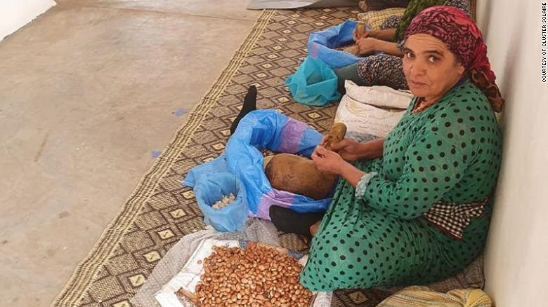 A woman crushing argan oil from the argan tree kernel using traditional methods at the  workshop.