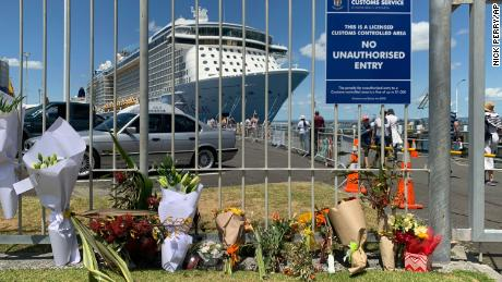 Flowers are laid at a makeshift memorial seen in front of cruise ship Ovation of the Seas, in Tauranga, New Zealand, Tuesday, December 10, 2019.