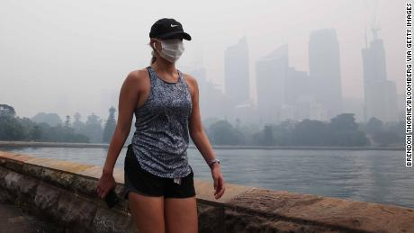 Bushfire smoke smothered Sydney on Tuesday, setting off fire alarms, suspending ferry services and triggering health warnings over choking air pollution.