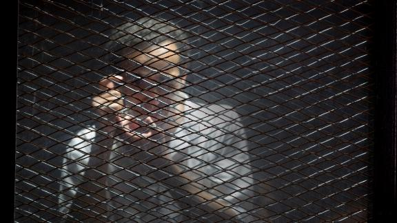 FILE - In this July 28, 2018 file photo, Egyptian photojournalist Mahmoud Abu Zied, known by his nickname Shawkan, gestures in a soundproof glass cage inside a makeshift courtroom in Tora prison in Cairo. Egypt has created a new high-powered human rights watchdog agency, but its primary mission isn