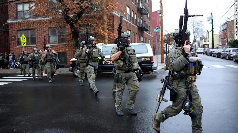 Police officers arrive at the active shooting scene in Jersey City on Tuesday.