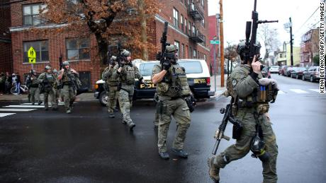Police officers arrive to the scene where an active shooting was taking place in Jersey City, New Jersey.