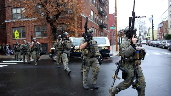 Police officers rush to the scene of an active shooting in Jersey City, New Jersey, on Tuesday.