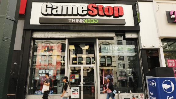 NEW YORK, NEW YORK - SEPTEMBER 16: People pass a GameStop store in lower Manhattan on September 16, 2019 in New York City.  GameStop has announced that it will close between 180 and 200 stores before the end of the fiscal year due to declining sales.  (Photo by Spencer Platt / Getty Images)