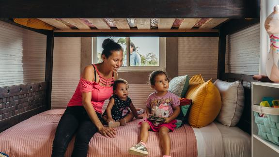 A family sits inside one of the two newly constructed 3D-printed homes in Mexico.