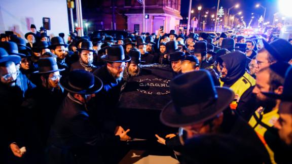 Orthodox Jewish men carry the casket of one of the victims of Tuesday