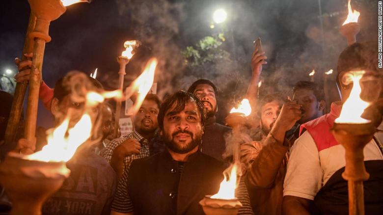 Demonstrators hold torches as they shout slogans against the government's Citizenship Amendment Bill (CAB), during a protest in New Delhi on December 11, 2019.