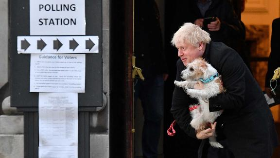 Johnson poses with his dog Dilyn as he leaves a polling station in London in December 2019.