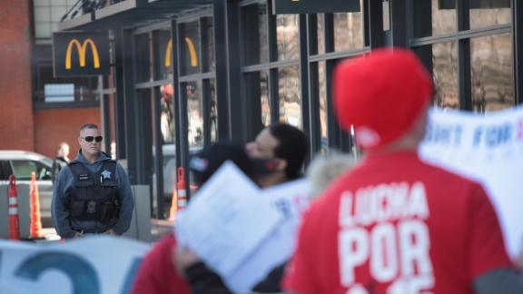 A police officer keeps watch as demonstrators march in front of the McDonalds Headquarters demanding a minimum wage of $15-per-hour and union representation on April 03, 2019 in Chicago, Illinois.