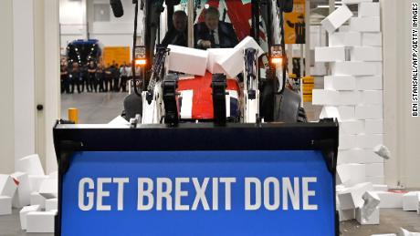 "Boris Johnson drives a Brexit-themed JCB through a fake wall emblazoned with the word ""GRIDLOCK,"" during the 2019 general election campaign."