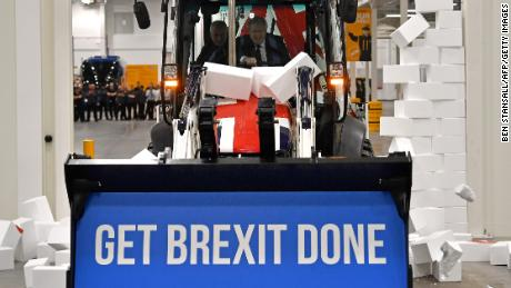 "TOPSHOT - Britain's Prime Minister and Conservative party leader Boris Johnson drives a Union flag-themed JCB, with the words ""Get Brexit Done"" inside the digger bucket, through a fake wall emblazoned with the word ""GRIDLOCK"", during a general election campaign event at JCB construction company in Uttoxeter, Staffordshire, on December 10, 2019. - Britain will go to the polls on December 12, 2019 to vote in a pre-Christmas general election. (Photo by Ben STANSALL / various sources / AFP) (Photo by BEN STANSALL/AFP via Getty Images)"